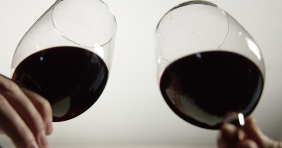 SLOW MOTION Two glasses of red wine toast in celebration against white background, closeup