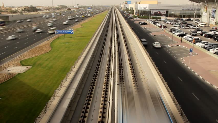Overground metro train EMU rush away along straight railway line. View from above, high angle perspective at red line flyover, elevated part of of Dubai Metro. Busy Sheikh Zayed roadway at left