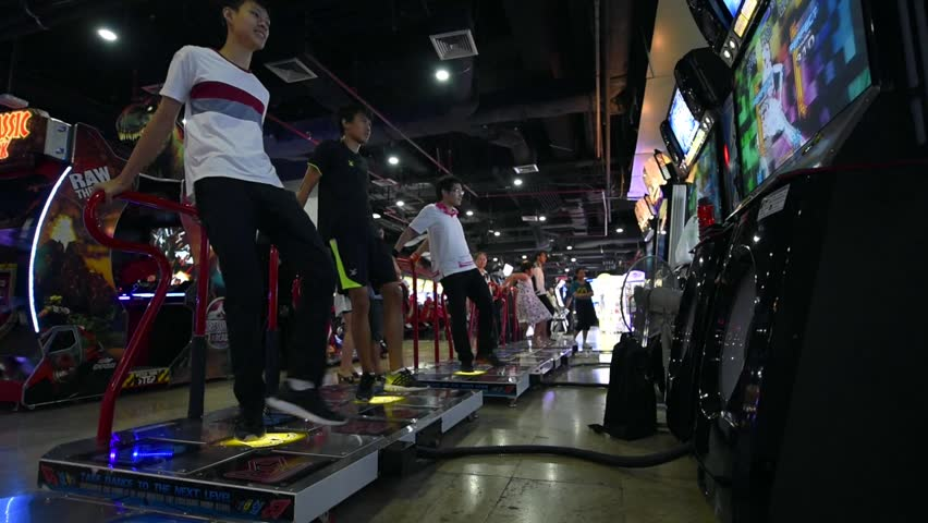 BANGKOK, THAILAND - 17 MARCH 2016: Boys playing popular dancing game Dance Dance Revolution Arcade, a popular exercise alternative for teens taken at FHD video