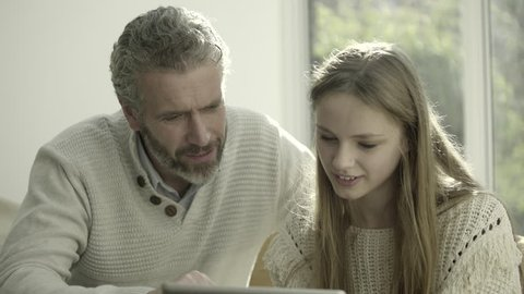 Father and teenage child at home looking at digital tablet