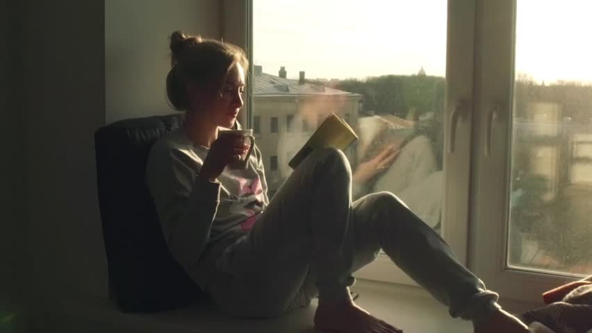 Beautiful young woman sitting on window sill with coffee end reading book on background of sunset | Shutterstock HD Video #15359098