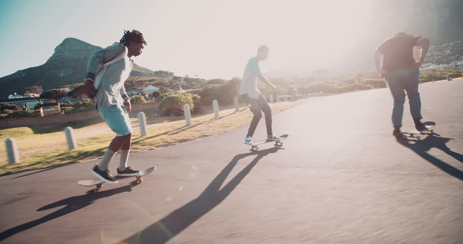 Multi-Ethnic group of skater friends skateboarding down road at seaside together during sunset #15362896