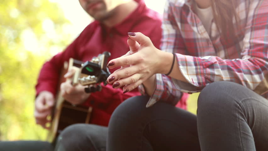 Close-up of man playing guitar while beautiful woman singing, graded #15380176