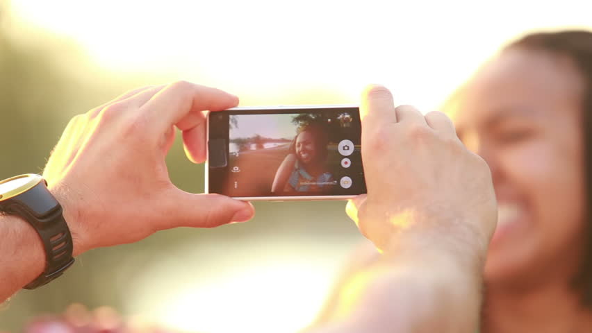 View of man's hand holding a mobile phone and taking pictures of woman at sunset. | Shutterstock HD Video #15398506