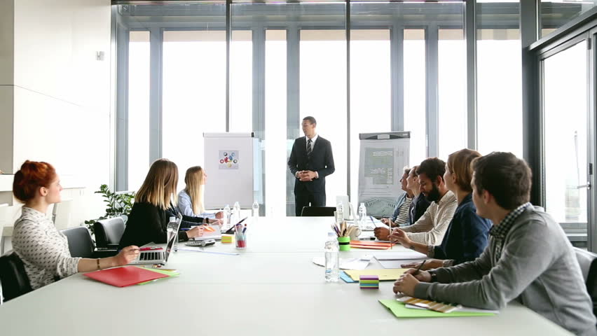Handsome young director pointing at flipchart during a meeting, graded | Shutterstock HD Video #15414616