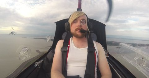 Portrait of young man with pince-nez in small gyrocopter in flight
