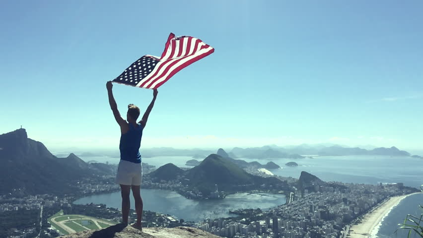 Man stands holding an American flag at a bright overlook of the city skyline of Rio de Janeiro, Brazil #15455296
