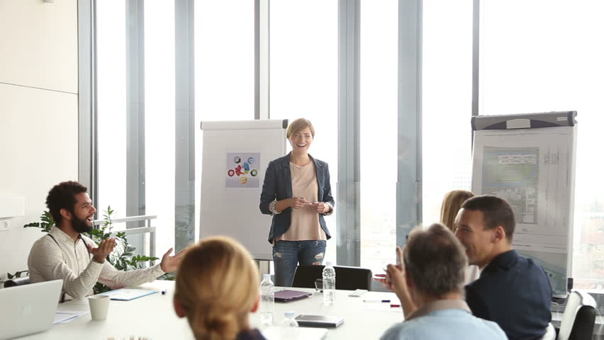 Happy Colleagues applauding to their beautiful female colleague after presentation, slow motion