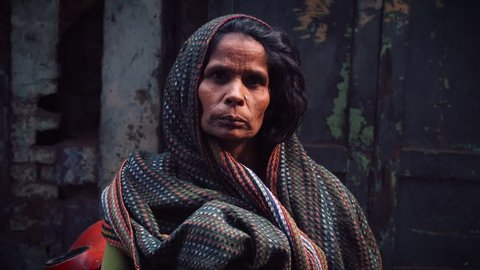 New Delhi, India - Circa 2013: Unidentified Indian woman beggar looking intently at camera with people passing by in New Delhi, India.