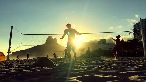 Silhouettes playing Brazilian beach futvolei (footvolley), a sport combining football (soccer) and volleyball, at sunset on Ipanema Beach, Rio