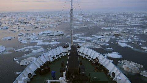 Research vessel in icy arctic sea on a sunny day