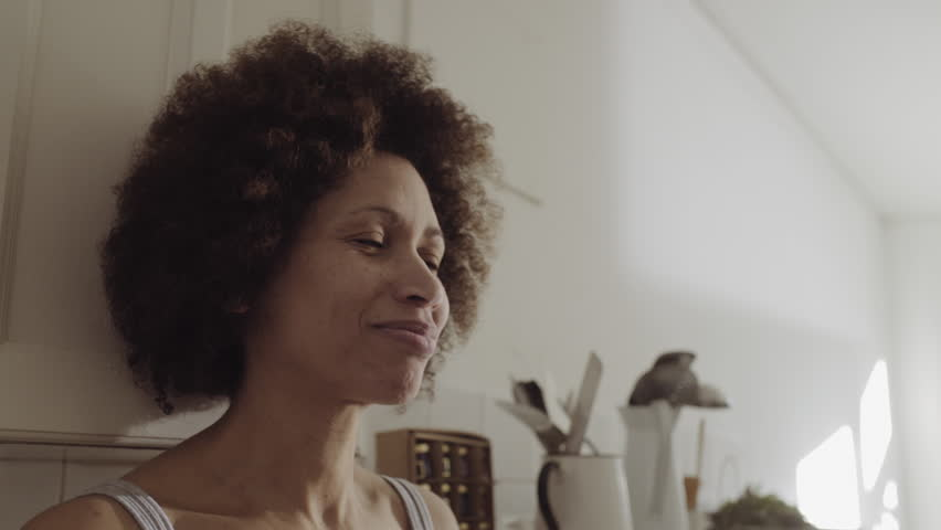 Afro American woman in kitchen enjoying coffee in the morning