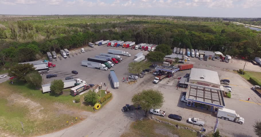Aerial over a busy truck stop with trucks,motorcycles and cars moving through to get gas, food and more. A great establishing shot before going inside building.
