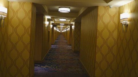 HOTEL HALLWAY POV.  STEADICAM SHOT WALKING DOWN THE NON-DESCRIPT HALLWAY OF AN UPSCALE HOTEL.