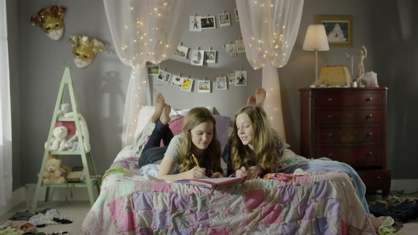 Medium shot of teenage girls doing homework on bed / Cedar Hills, Utah, United States | Shutterstock HD Video #15521524