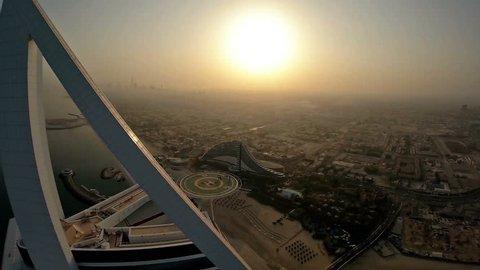 Fly over Jumeirah Beach near Burj Al Arab hotel in Dubai, UAE. Burj Al Arab is a luxury 5 star hotel built on an artificial island in front of Jumeirah beach. Helicopter aerial view at sunrise