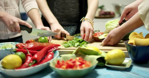 Several hands preparing for a taco tortilla dinner in a kitchen. Cutting fresh vegetables on a wooden bench in a modern kitchen with shallow focus and blurred background. Strong and vivid colors.