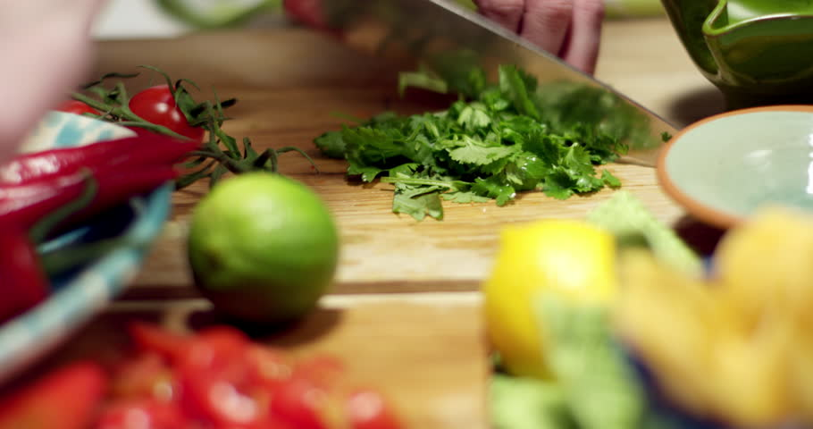 Preparing for a taco tortilla dinner in a kitchen environment. Cutting fresh vegetables on a wooden bench in a modern kitchen with shallow focus and blurred background. Strong and vivid colors.