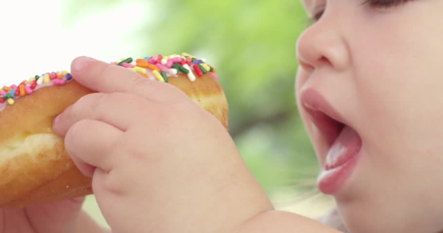 RED 2K slow motion shot of a child eating a doughnut in slow motion. As the child is chewing sprinkles fall.