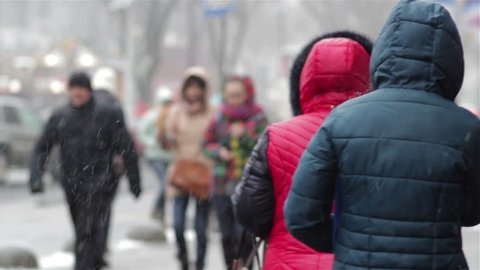 People snow and rain/bad weather in precipitation  snow and rain on the street people go