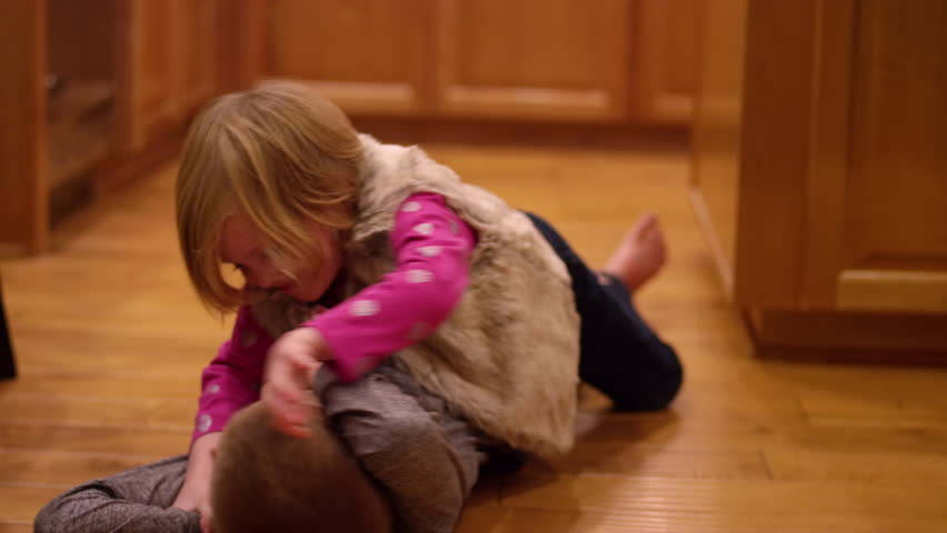 Young siblings wrestling and play fighting in the kitchen at home