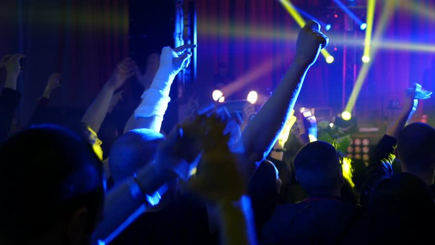 KHERSON, UKRAINE - MAR 26, 2016 - Free public music concert - Clapping fan spectators silhouettes at a concert flashing lumiere sway raise hands | Shutterstock HD Video #15622042