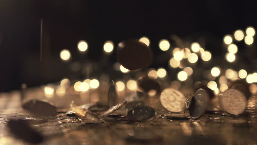 Pile of coins falling on the yellow table. Economic and financial crisis. Salary fall and pension increase, heap or bunch funds for shopping for people. Close up of capital indoors. Macro slow motion