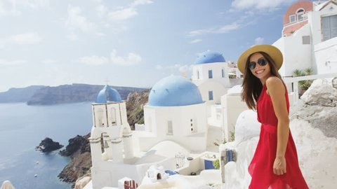 Woman tourist in red dress walking on steps in Oia, Santorini, Greek Islands, Greece, Europe. Asian on travel enjoying vacation visiting famous tourist attraction destination, Blue Domed Church.