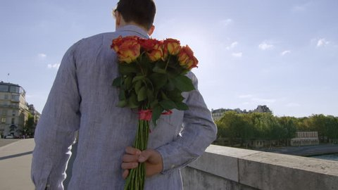 Young man gives his lady a bunch of roses and a big kiss while in Paris- Paris, France
