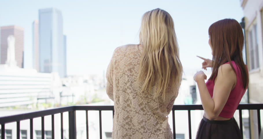 Two attractive young women pointing to various buildings and other things from a balcony in Downtown Los Angeles. Slow motion, recorded hand-held in 4K at 60fps. | Shutterstock HD Video #15696820