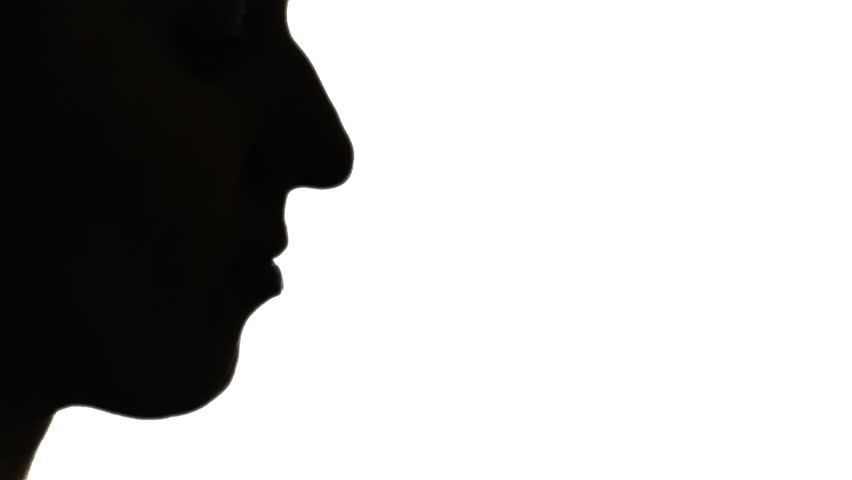 Silhouette shot of a woman blowing into a whistle.