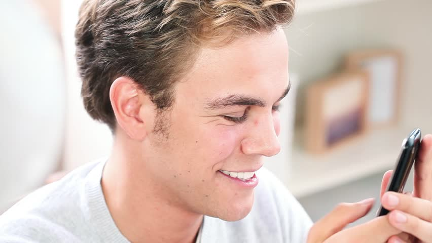 young man sending sms, using phone