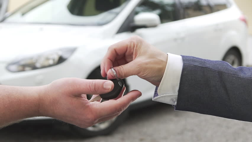 Car sale. A man selling a car to another man and handing over the key.   Shutterstock HD Video #15732757