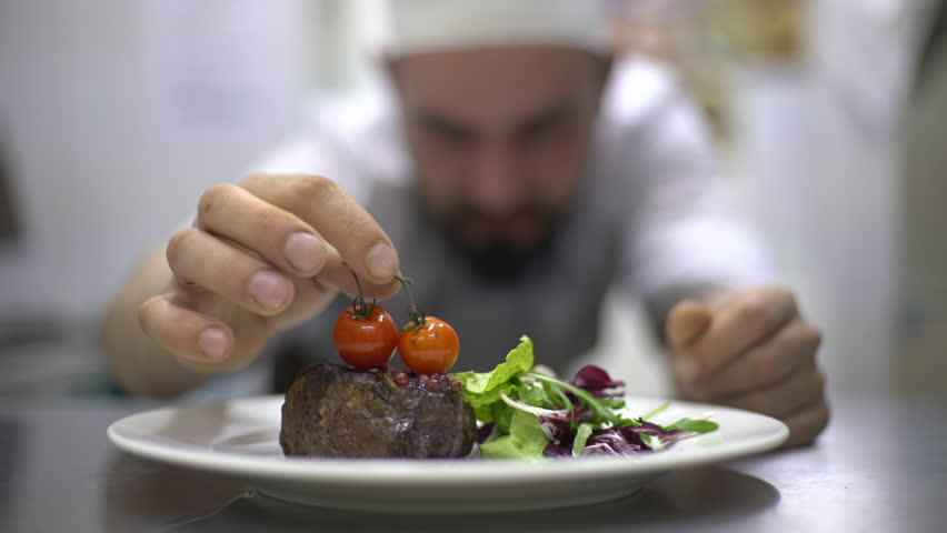 Chef is finishing meal teasty beef steak with salad for guest of restaurant. Final touch tomatoes | Shutterstock HD Video #15732823