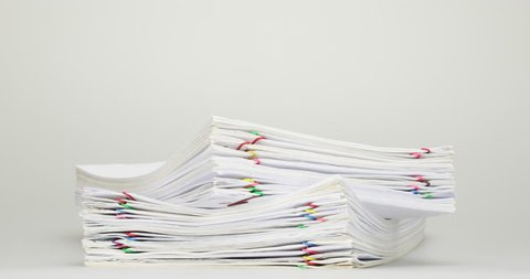 Stack overload document of receipt and report with colorful paperclip place on white table time lapse. Pile of document is increasing as work is going to be successful. Business concept footage.