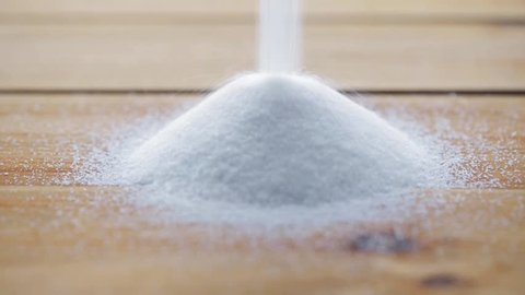 food, junk-food, cooking and unhealthy eating concept - white sugar pouring into heap on wooden table