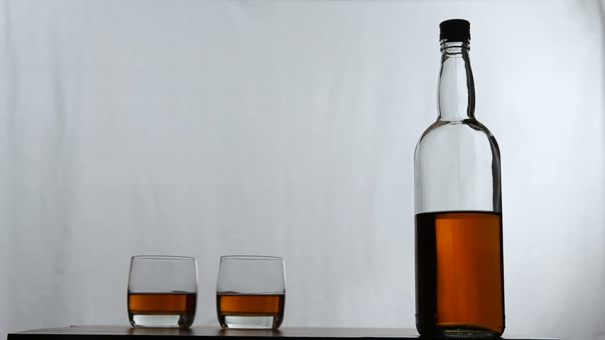 Two glasses of whiskey with a bottle in the white background.Rotating glasses of whiskey with bottle. | Shutterstock HD Video #15759316