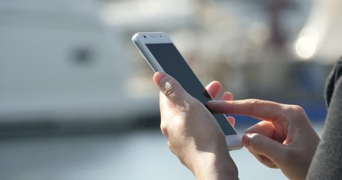 4k A girl using a smartphone at seaside,yacht & sailing in the harbour. gh2_11093_4k