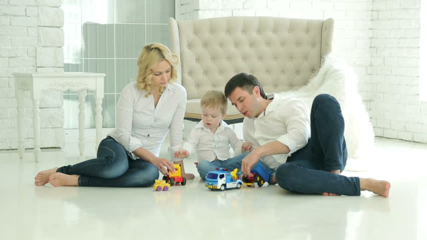 Mom Dad And Son On The Floor. Son Playing Toy Car. Happy European Family.  On The Background Of White Floor And Sofa, A Window And White Brick Walls  Stock ...