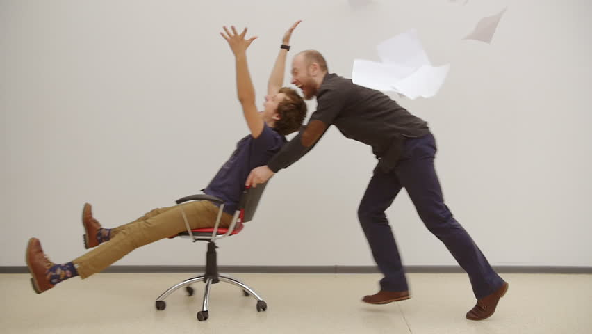 Office chair race. Slow motion. Young guys have fun in the office during a break. Games of businessmen from large offices. Men celebrate a successful deal and throwing papers up. Office party. | Shutterstock HD Video #15778099