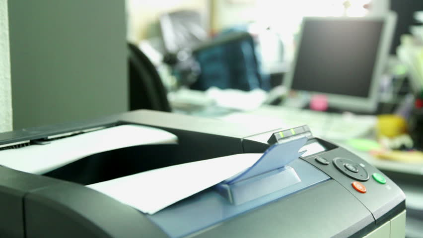 Printing document paper with laser printer. Office work and furnishings, stationery around in the background is seen the monitor