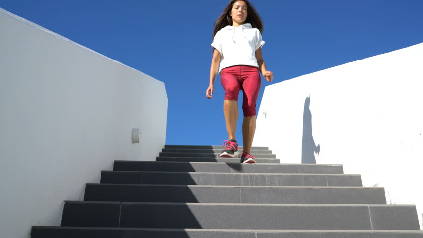 Stairs running woman doing run on steps down staircase. Female runner athlete jogging on stairs in sport workout run outside.