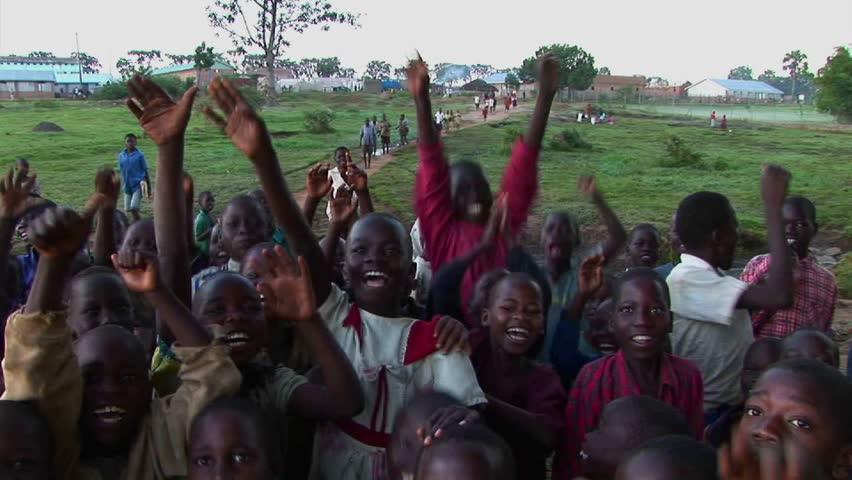 UGANDA, AFRICA - CIRCA 2009: Crowd of children at a refugee camp wave at the camera circa 2009 in Uganda.