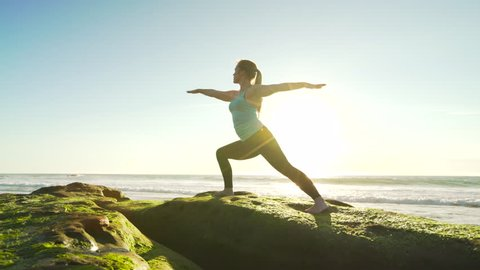 Happy young woman practicing yoga on the beach at sunset. Healthy active lifestyle concept. 4K