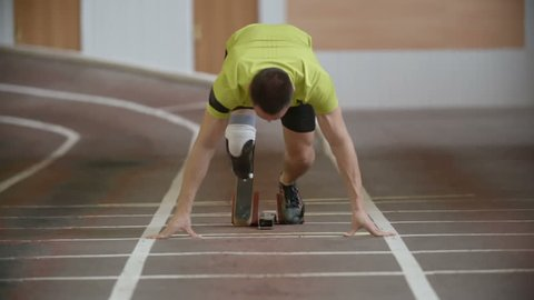Young determined amputee athlete with artificial leg starting from blocks and running towards the camera in slow motion