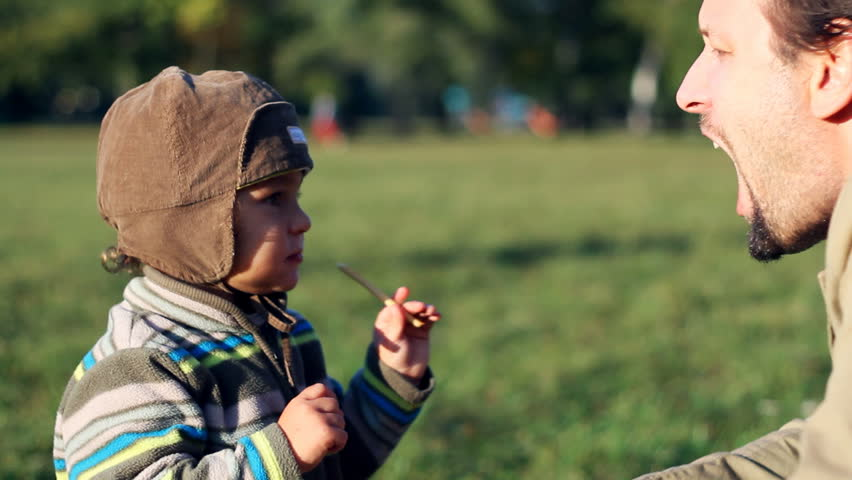 Young child feeding his father with snack, outdoors