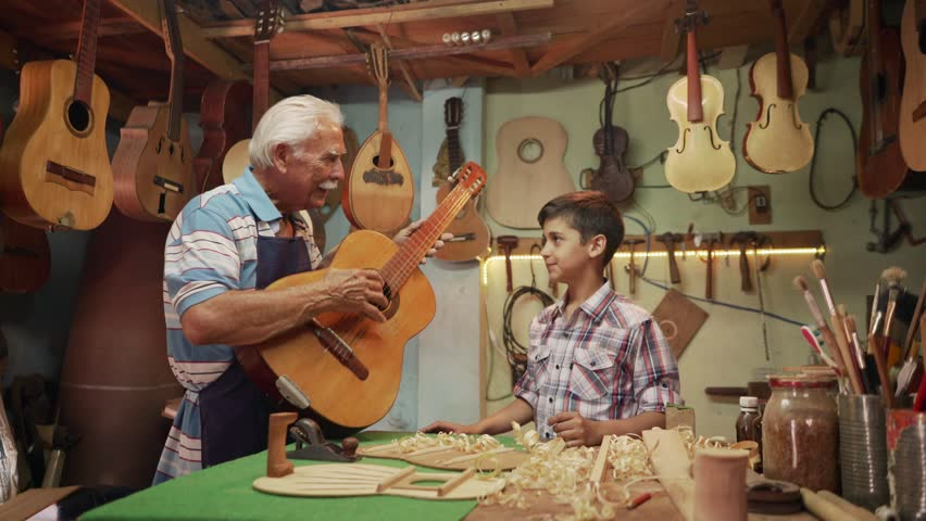 Generations and family business, old and young people showing love for music. Boy and senior man, happy kid and elderly person, grandfather teaching child how to play guitar in workshop  | Shutterstock HD Video #15839716