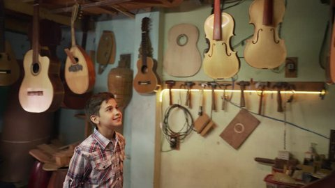 Young people showing love for music. Hispanic boy, happy kid, grandson with guitars and instruments in lute maker shop. Child smiling, looking at classic guitar and musical instrument