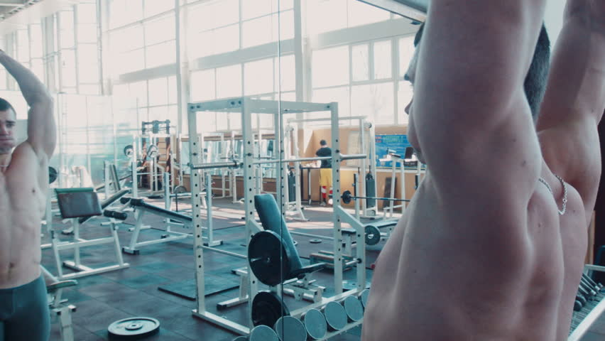 Bodybuilder does movement exercise for back and shoulders, with barbell in gym near mirror. Movement stabilizer shot | Shutterstock HD Video #15851953