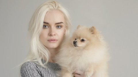 Cinemagraph Beautiful Blonde Woman With Her Spitz Isolated On Grey